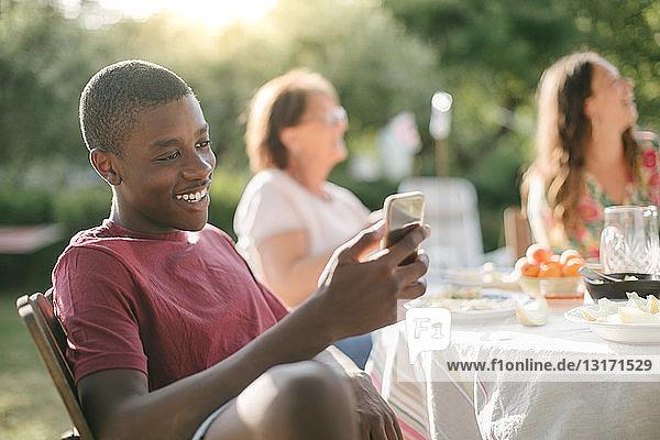 Junge lächelt beim Benutzen eines Mobiltelefons im Garten während einer Gartenparty