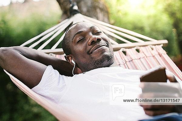 Lächelnder Mann mit geschlossenen Augen genießt Musik über Mobiltelefon  während er sich auf der Hängematte entspannt