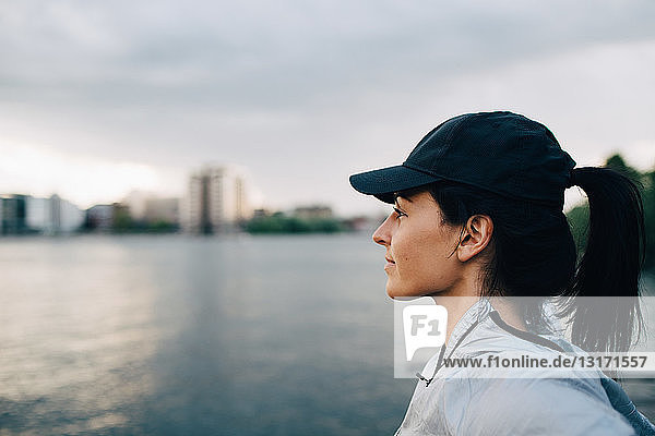 Side view of female athlete looking away while standing by sea against sky