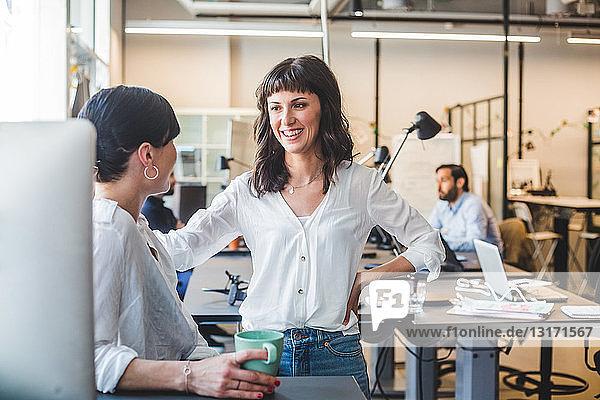 Weibliche Mitarbeiter  die sich unterhalten  während sie im Büro am Schalter stehen