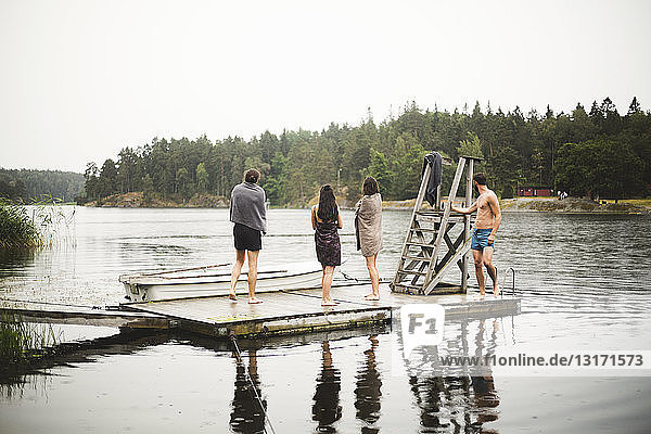 Friends wrapped in towels standing on jetty over lake against clear sky