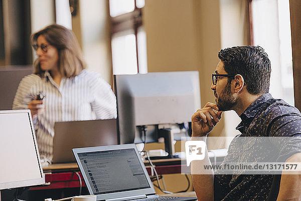Mittelgroßer Geschäftsmann schaut sich eine Kollegin im neuen Büro an