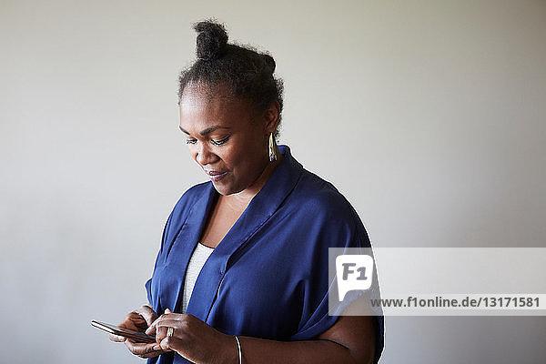 Kreative Geschäftsfrau mit Smartphone gegen graue Wand im Büro