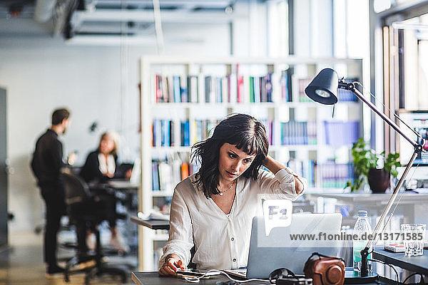Geschäftsfrau schaut auf den Laptop  während sie im Büro sitzt