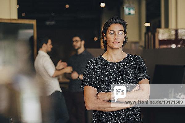 Porträt einer Geschäftsfrau mit verschränkten Armen und Kollegen im Hintergrund im Büro
