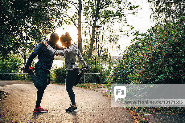 Full length of male and female athletes stretching legs while standing on road in park