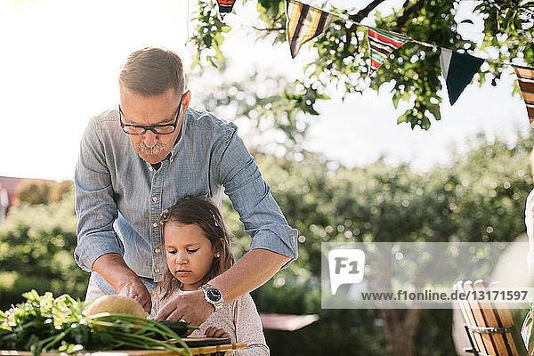 Großvater lehrt Enkelin  Gemüse bei Tisch im Hinterhof zu schneiden