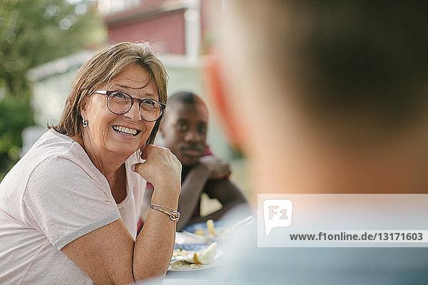 Lächelnde ältere Frau schaut weg  während sie während der Gartenparty am Tisch sitzt
