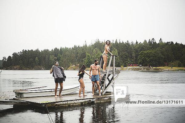 Männliche und weibliche Freunde stehen auf dem Steg über dem See vor klarem Himmel während eines Wochenendausflugs