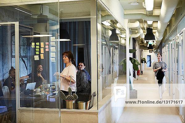 Geschäftsleute beim Brainstorming von Ideen im Sitzungssaal  während eine Kollegin im Korridor geht