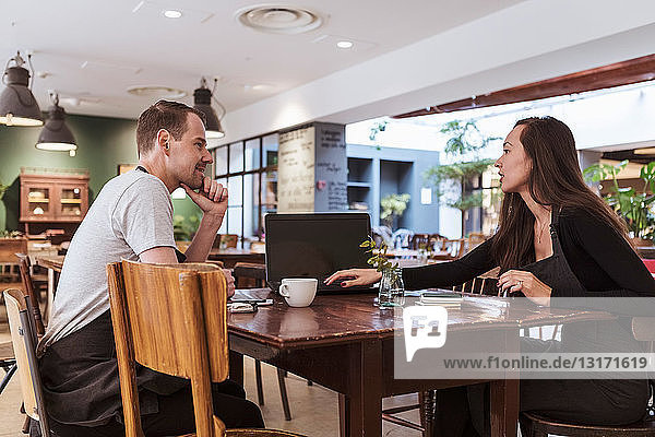 Male and female partners using laptop at table in cafe