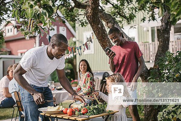 Junge fotografiert Schwester und Vater bei der Zubereitung des Essens am Tisch im Hinterhof während einer Gartenparty