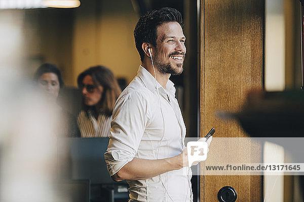 Lächelnder mittelgroßer Mann mit Kopfhörern  der im Büro mit einem Smartphone telefoniert