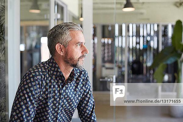 Nachdenklicher  reifer Geschäftsmann schaut weg  während er in einem kreativen Büro sitzt