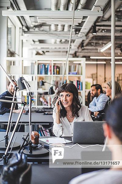 Unternehmerin schaut weg  während sie am Schreibtisch im Kreativbüro mit dem Handy telefoniert