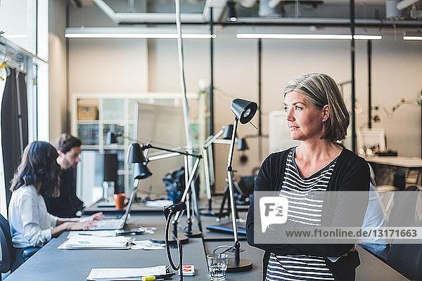 Selbstbewusste Geschäftsfrau schaut weg  während sie im Kreativbüro am Schreibtisch steht