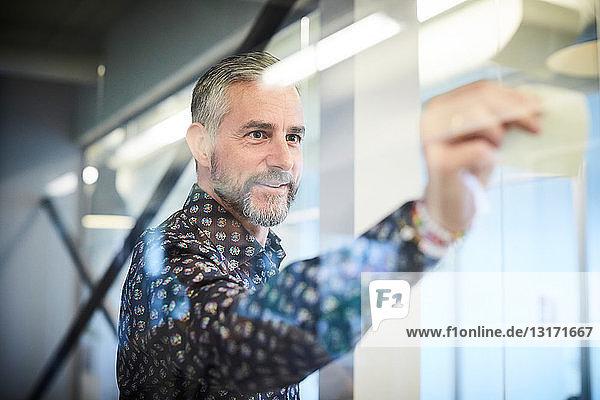 Reifer Geschäftsmann klebt Klebezettel auf Glas im Sitzungssaal