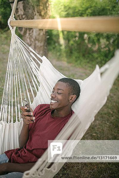Lächelnder Junge benutzt Mobiltelefon  während er sich auf einer Hängematte im Hinterhof entspannt