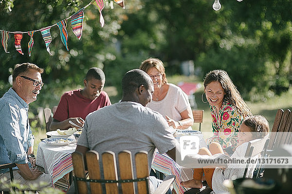 Glückliche Mehrgenerationen-Familie beim gemeinsamen Mittagessen im Garten während der Gartenparty