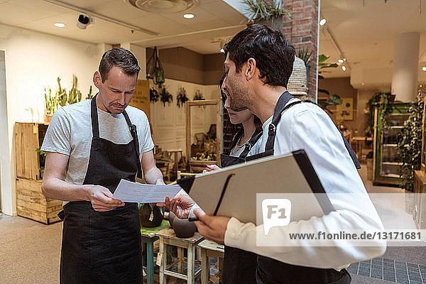 Männlicher Eigentümer diskutiert über Dokument mit Kollegen im Geschäft