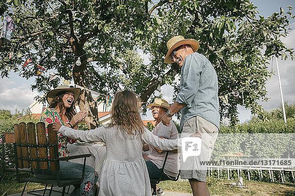 Familie applaudiert beim Anblick eines älteren Mannes und eines Mädchens  die während einer Gartenparty tanzen