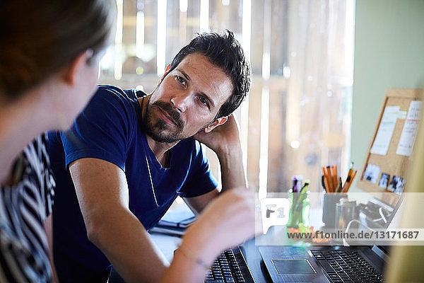 Geschäftsfrau diskutiert mit männlichem Kollegen am Computerschreibtisch im Kreativbüro