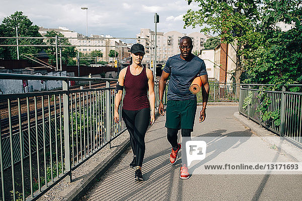 Multi-ethnic male and female athletes talking while walking on footbridge in city
