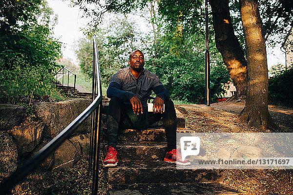 Portrait of confident male athlete sitting on steps at park