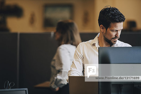 Mid adult businessman using laptop in creative office