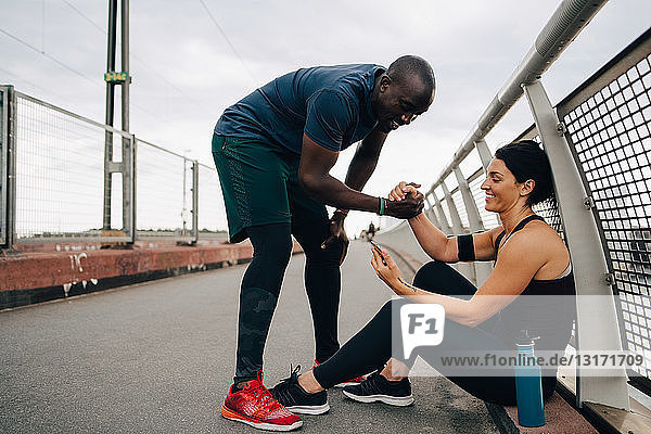 Cheerful male and female athletes holding hands while looking at mobile phone on footbridge