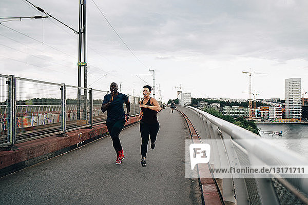 Full length of male and female athletes running on footbridge in city