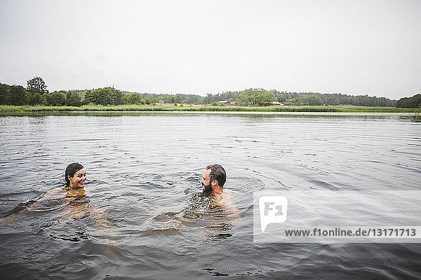 Glückliche männliche und weibliche Freunde schwimmen am Wochenende im See bei klarem Himmel
