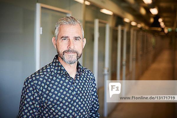 Porträt eines selbstbewussten  reifen Geschäftsmannes  der im Korridor eines kreativen Büros steht