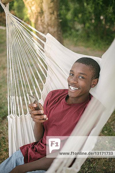 Porträt eines lächelnden Jungen  der ein Mobiltelefon benutzt  während er auf einer Hängematte im Hinterhof liegt