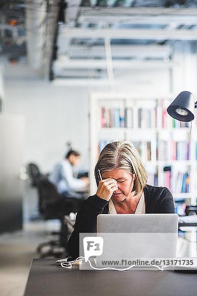 Müde Geschäftsfrau mit Laptop am Schreibtisch im Kreativbüro