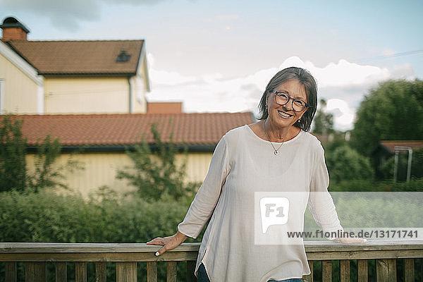 Porträt einer älteren Frau  die vor dem Geländer der Veranda steht