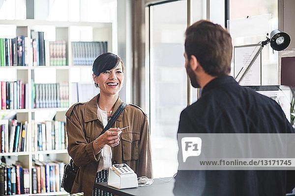 Geschäftsfrau lächelt  während sie am Schalter im Büro eine Karte an einen männlichen Unternehmer erhält