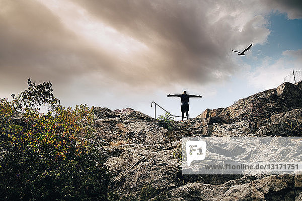 Low angle view of male athlete standing with arms outstretched on hill against sky