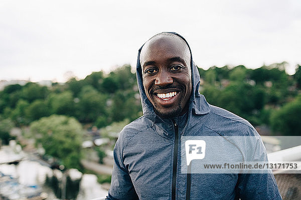 Portrait of confident male athlete standing on footbridge
