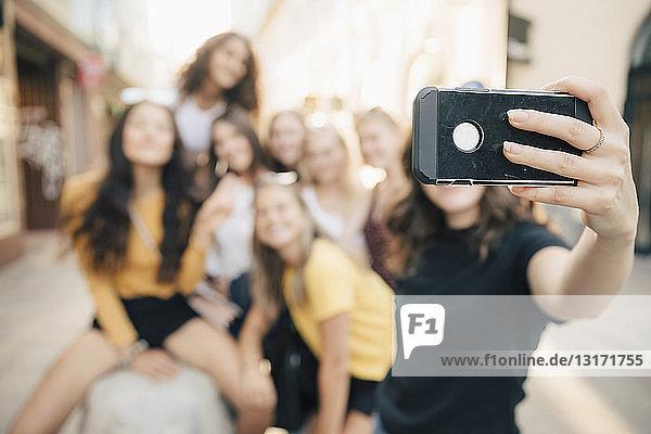 Junge Frau  die in der Stadt mit Freunden per Smartphone Selbsthilfe betreibt