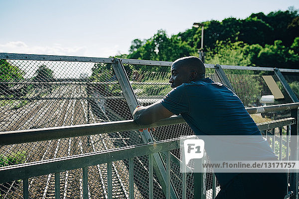 Tired sportsman looking away while leaning on railing at bridge