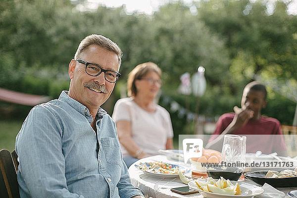 Porträt eines älteren Mannes  der lächelt  während er während einer Gartenparty gegen die Familie am Tisch sitzt