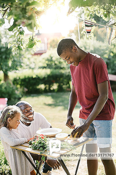Junge schneidet Melone auf dem Tisch  während Vater und Schwester ihn während der Gartenparty anschauen