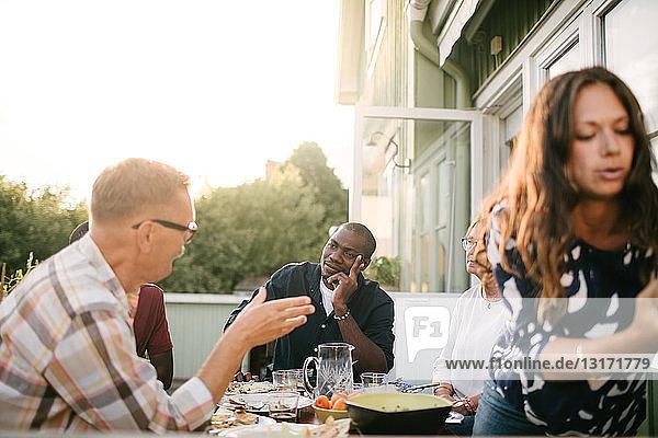 Mehrgenerationen-Familie unterhält sich beim Mittagessen am Tisch auf der Veranda