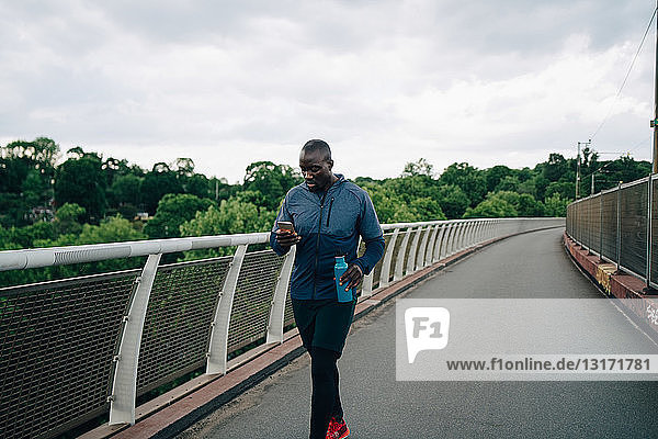 Male athlete using mobile phone while walking on footbridge against sky in city