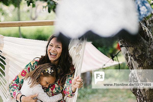 Fröhliche Mutter schaukelt mit Tochter auf Hängematte im Hinterhof