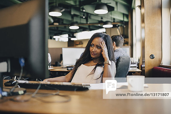 Concentrated businesswoman looking at computer monitor in office