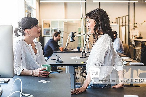 Weibliche Kollegen im Gespräch am Schalter im Büro