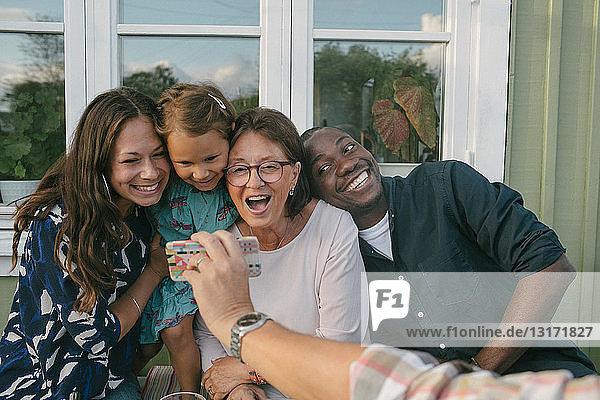 Ausgeschnittenes Bild eines Mannes  der auf der Veranda ein Mobiltelefon einer fröhlichen Familie zeigt