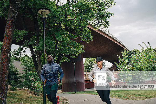 Male and female athlete running on footpath in city